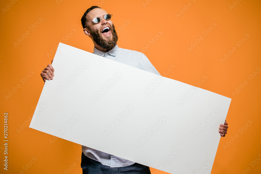 Fototapety, obrazy: Hipster man holding a poster with blank space for your text.