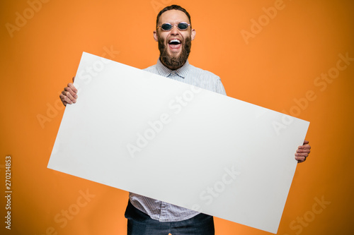 Obraz Hipster man holding a poster with blank space for your text. - fototapety do salonu