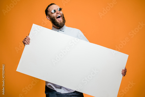 Fotografía  Hipster man holding a poster with blank space for your text.