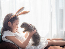 Kind Little Cute Girl 5-6 Years Old Sitting And Holding A Gray Rabbit Near The Window. A Girl With A Gentle Heart, Loves Animals. Lovely Kid And Gray Rabbit.