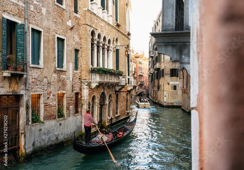 Fotografía  Venetian gondolier punts gondola through narrow canal waters of Venice Italy