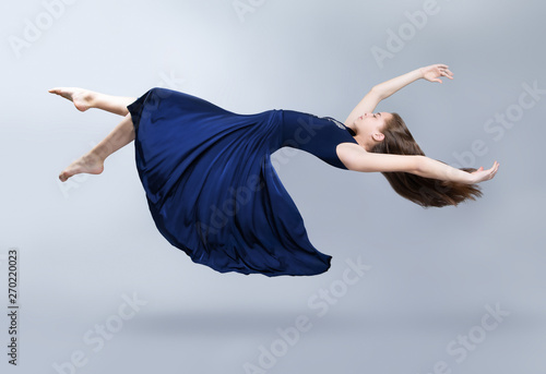 Fotografia, Obraz A girl in a blue dress is floating in the air
