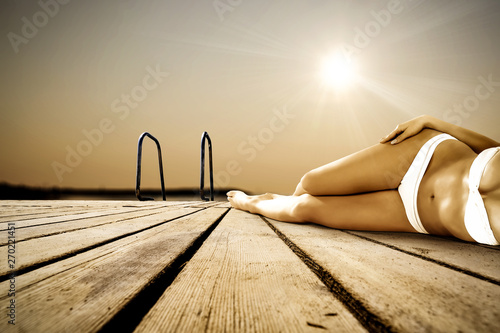 Wooden pier and landscape of sea with slim young woman body in bikini.