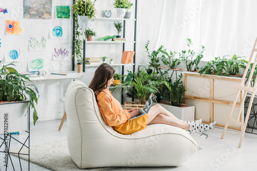 Photo  young woman using laptop while sitting on soft chaise lounge in light spacious r