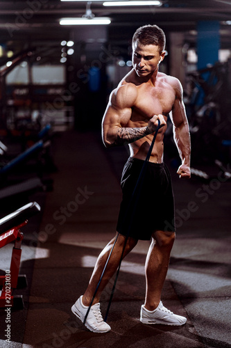 Stampa su Tela Hard working well built sportsman exercising with a resistance band in gym