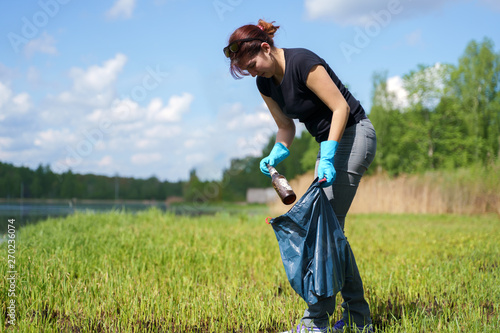 Fotografie, Obraz  Image of side of young woman in rubber gloves picking up garbage in bag on bank