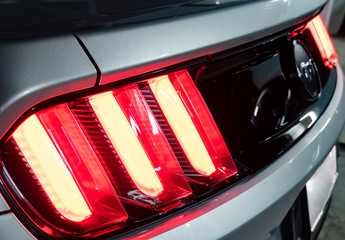Bangkok -Thailand  May 28, 2019: The tail light of a silver 2015 50th Anniversary Ford Mustang with water drops on the car.