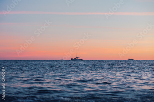 Valokuva  Lonely boat floats on a quiet warm calm sea against the backdrop of a golden sunset on a warm summer evening