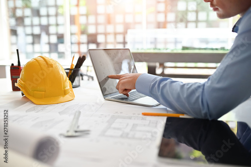 Fotomural Architect man working on blueprint with engineer planing on office desk