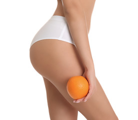 Closeup view of slim woman in underwear with orange on white background. Cell...