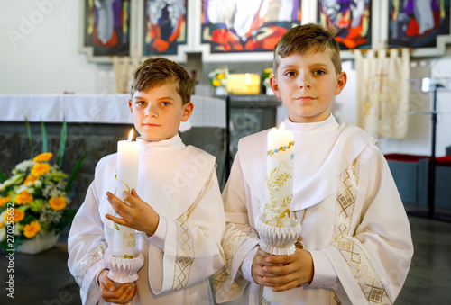Foto  Two little kids boys receiving his first holy communion