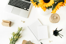 Home Office Desk Workspace With Laptop, Notebook, Clipboard, Yellow Sunflowers Bouquet On White Background. Flat Lay, Top View Freelancer / Blogger Work Concept.