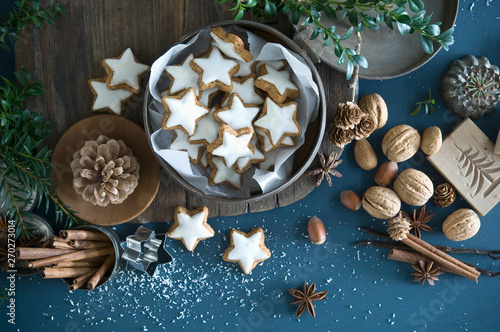Cinnamon stars in tin can, star anise, cinnamon sticks, nutcracker and pine cones