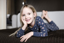 Portrait Of Smiling Little Girl With Tooth Gap Relaxing On Couch At Home
