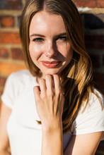 Young Woman In Front Of Brick Wall, Portrait