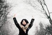 Happy Asian Young Woman Enjoying A Winter Storm Outside