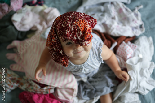 Obraz big pile of clean clothes and baby playing - fototapety do salonu