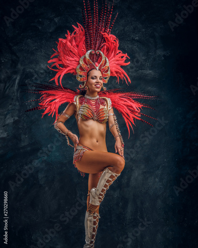 Spoed Foto op Canvas Carnaval Happy beautiful brasil dancer in red feather costume is dancing on small scene.