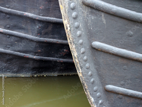 a close up of the bows of two moored old fashioned narrowboats painted black wit Fotobehang
