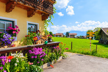 Traditional Alpine House Decorated With Flowers In Village Of Going Am Wilden Kaiser On Beautiful Sunny Summer Day With Alps Mountains In Background, Tirol, Austria