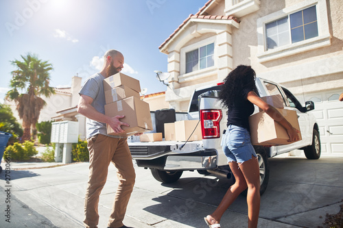 Photo  interracial couple moving into new home and taking boxes out of truck