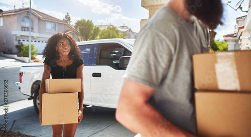 interracial couple moving into new home and taking boxes out of truck Wallpaper Mural