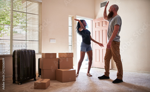 Canvastavla  interracial couple giving each other a high five afrer moving into new house