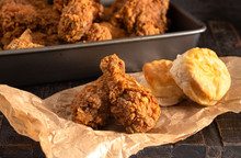 Crispy Chicken Drumsticks With Buttermilk Biscuits On A Rustic Wooden Table