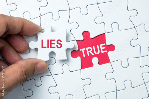 Photo True word on missing puzzle with a hand hold a piece of lies word puzzle