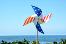 A Red White And Blue Patriotic Pinwheel With Blue Sky And Ocean