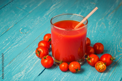 Tomato juice in glasses on blue wooden table.