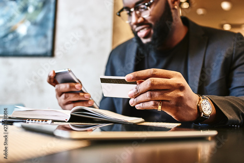 Fotografia Shot of african american businessman holding mobile and credit card, while resti