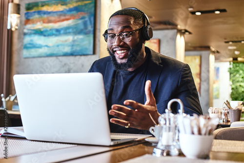 Work until you no longer need to introduce yourself. Young businessman with headphones sitting in cafe in front of laptop and networking - 270331490