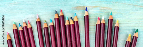 Pinturas sobre lienzo  A panoramic view of many colored pencils, shot from the top on a vibrant teal bl