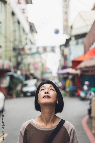 Photo  mature Asian woman wait and see