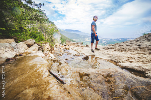 Fototapeta Man stands at the edge of a rock. obraz na płótnie