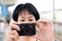 Mature Asian Woman Using Digital Camera