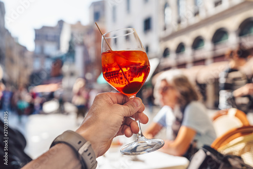 Man's hand with a glass of aperol Fototapeta