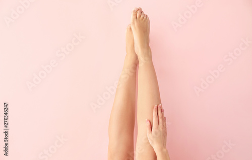 Beautiful young woman after laser hair removal procedure of legs on color backgr Canvas Print