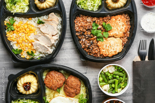 Photo  Containers with delicious food on grey background