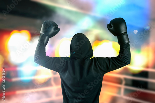boxer without a name closed by a black overalls raised his hands up in a winning gesture on the sports ring in the light of spotlights Tablou Canvas