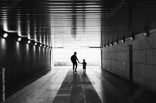 Papiers peints Tunnel Silhouettes in the tunnel - man and little child walking through empty, dark corridor. Underground passage. Unpleasant, dark place. Kidnapping, stranger, danger, child safety concept. Black and white