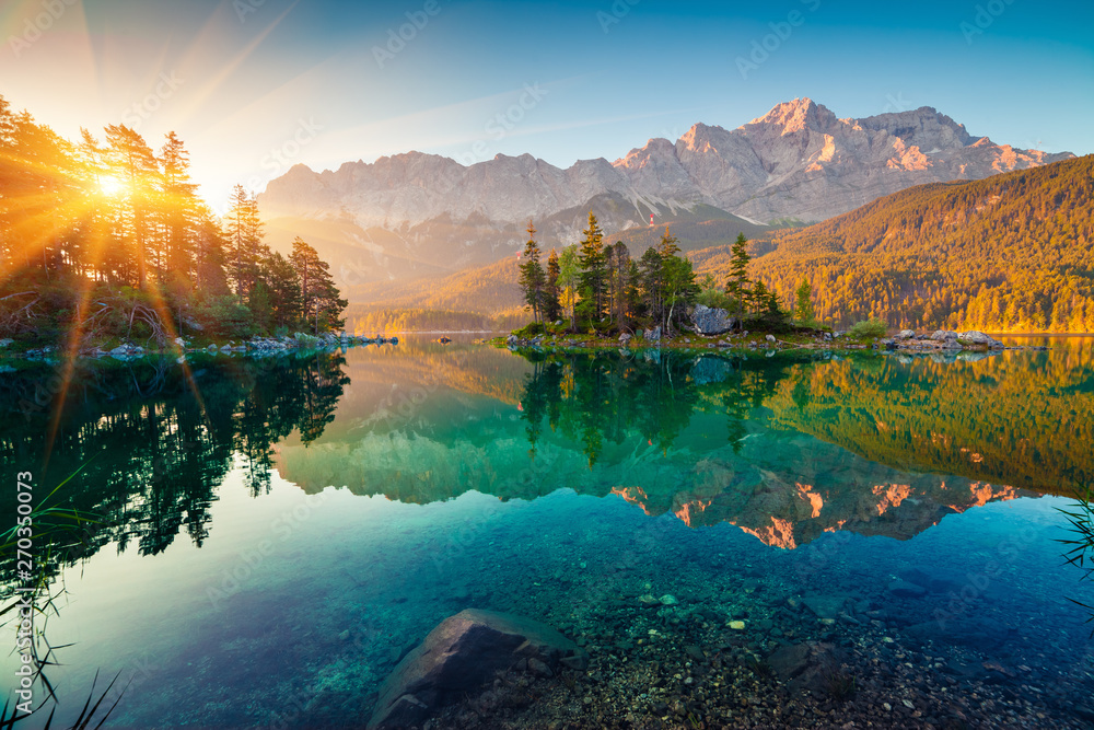 Fototapeta Impressive summer sunrise on Eibsee lake with Zugspitze mountain range. Sunny outdoor scene in German Alps, Bavaria, Germany, Europe. Beauty of nature concept background.