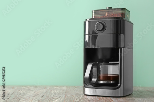 Modern coffee machine on table against color background