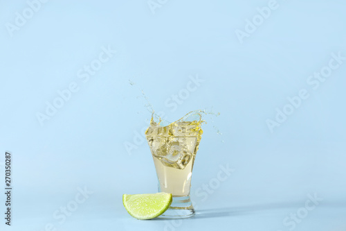 Obraz na plátně Shot of tequila with splash on light background