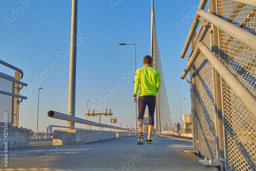 Fototapeta Sportsman working out / jogging on a big city urban bridge. obraz na płótnie