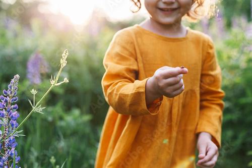 Valokuva Adorable little girl wearing mustard linen dress with ladybug among lupine flowe
