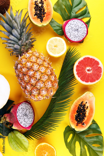 Leinwand Poster Exotic fruits and tropical palm leaves on pastel yellow background - papaya, man