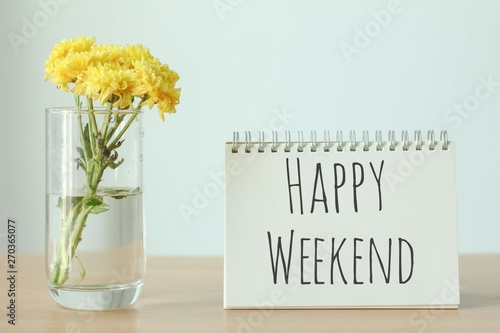 Fotografía Yellow flower in glass with happy weekend notebook on wood table on white background