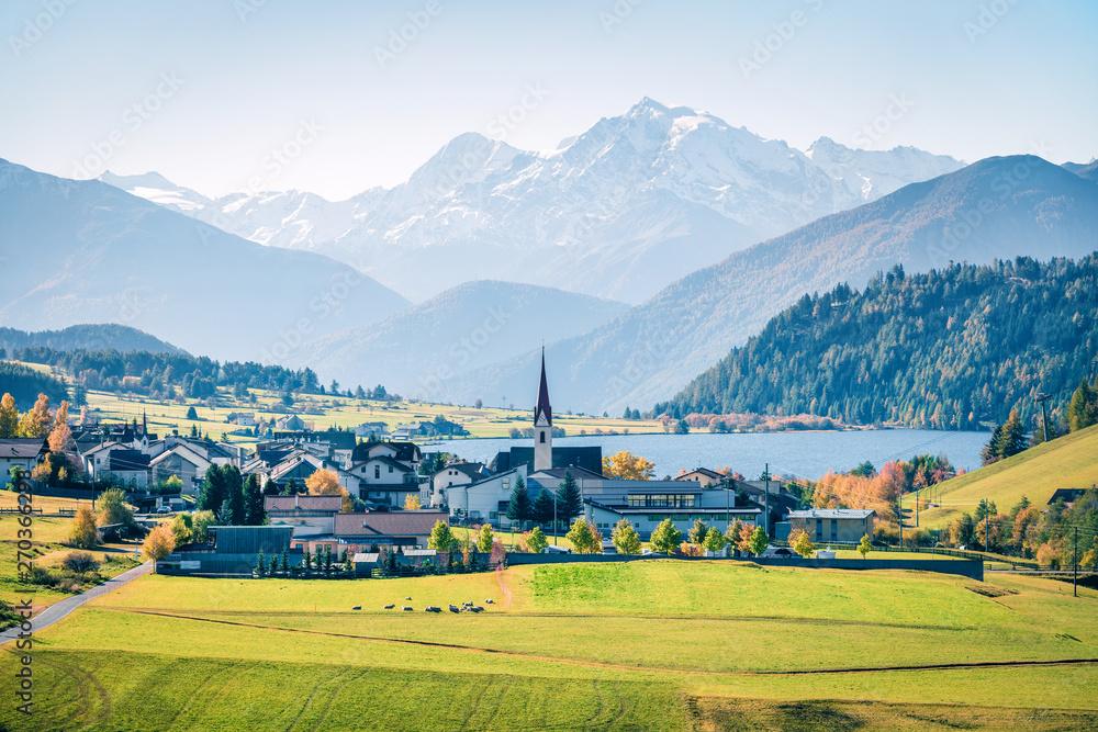 Fototapeta Splendid autumn view of San Valentin village. Colorful morning scene of small Italian village located on shore of Muta lake, South Tyrol, Italy, Europe. Instagram filter toned.